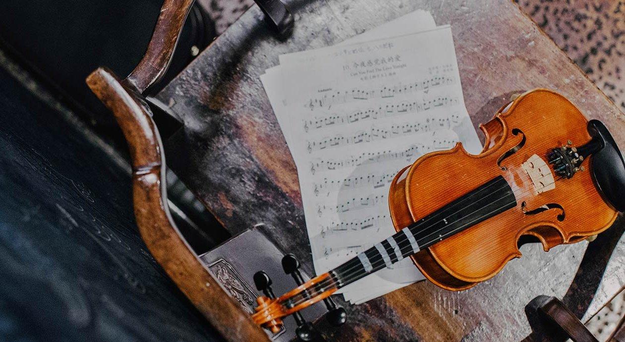 Violine und Notenblätter auf altem Holzstuhl